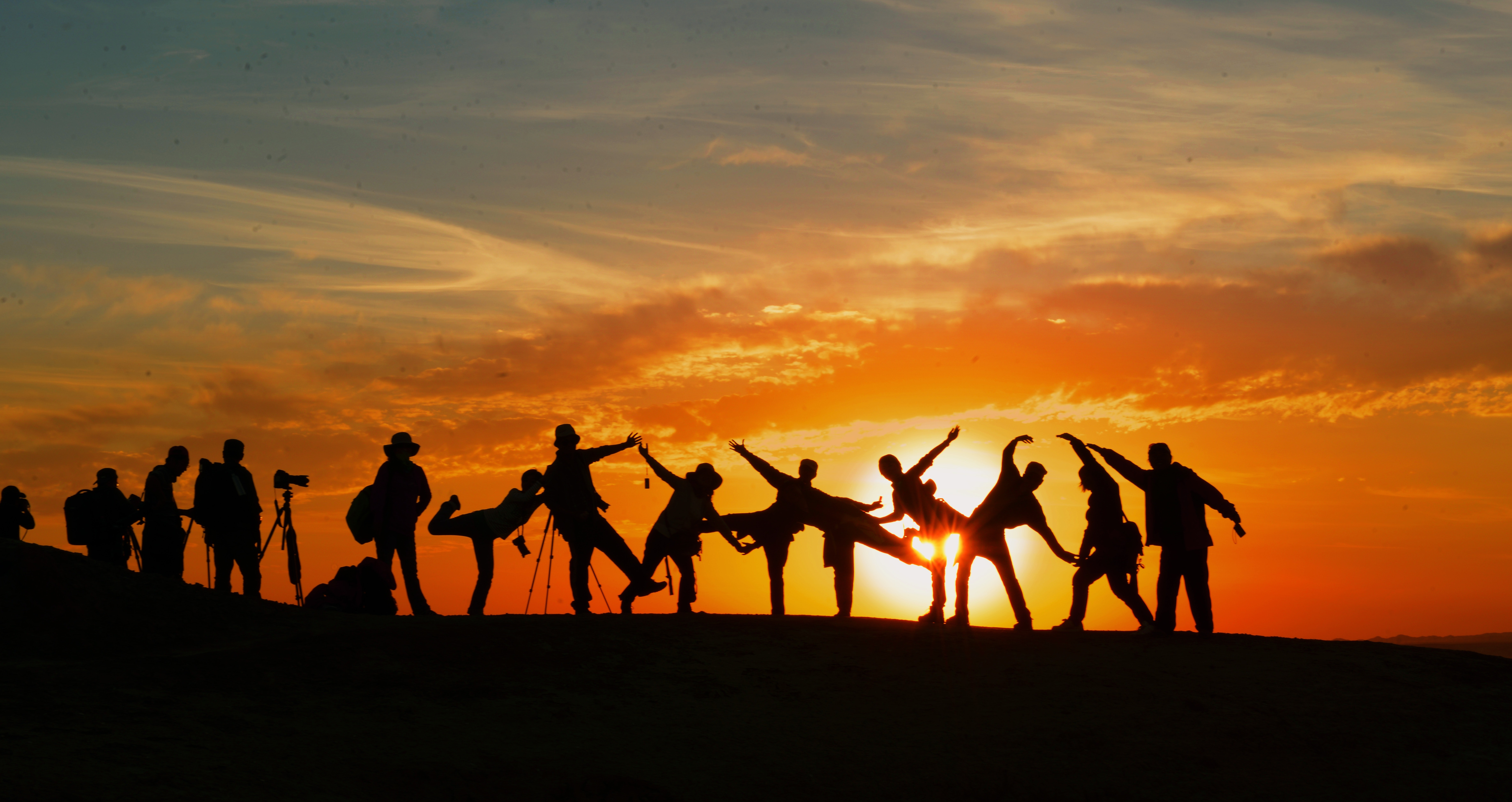 Individuals posing for photo during sunset
