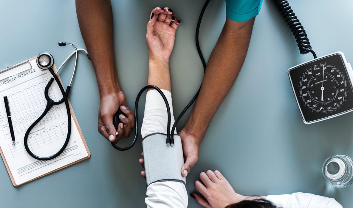 Doctor recording patients blood pressure
