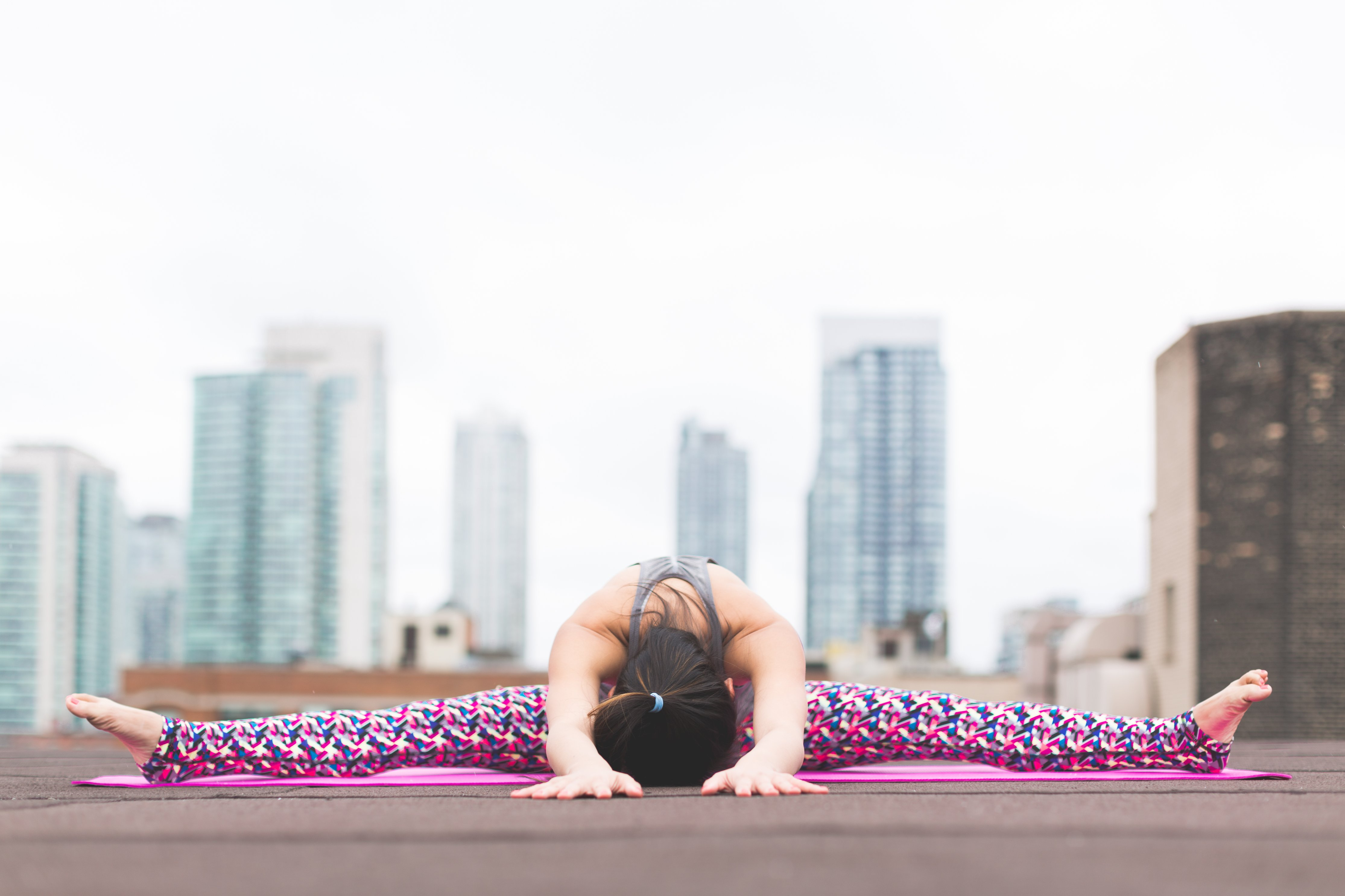 Women doing yoga with city skyline in the back